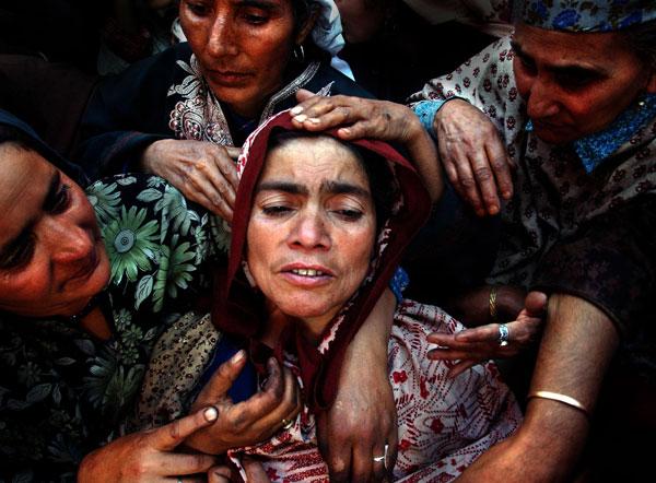 © Ami Vitale, Gujarat, Hindistan : Çocuğunun öldüğünü az önce öğrenen kadını arkadaşları sakinleştirmeye çalışıyor. | Duygu, Işık Kalitesi, Grafik